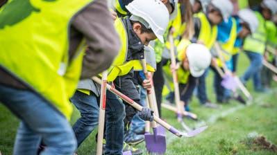 Mit Schaufeln versuchen die Kinder mit dem Aushub für die Turnhalle zu beginnen. Auf Schulbeginn 2020 soll der Bau fertig sein. (Bilder. Andrea Stalder)