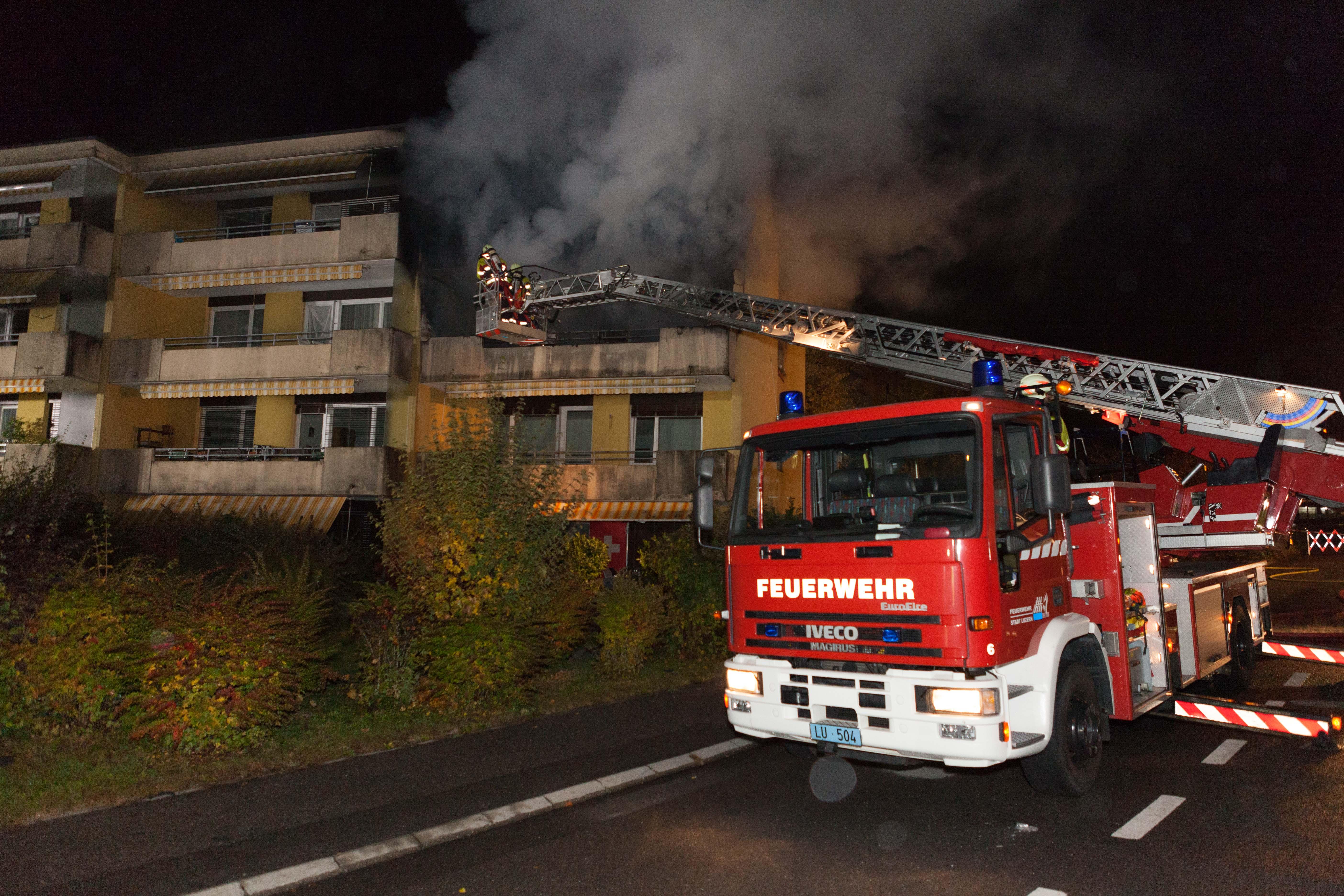 Den Einsatzkärften auf der Drehleiter quillt dunkler Rauch entgegen. (Bild: Feuerwehr Stadt Luzern)