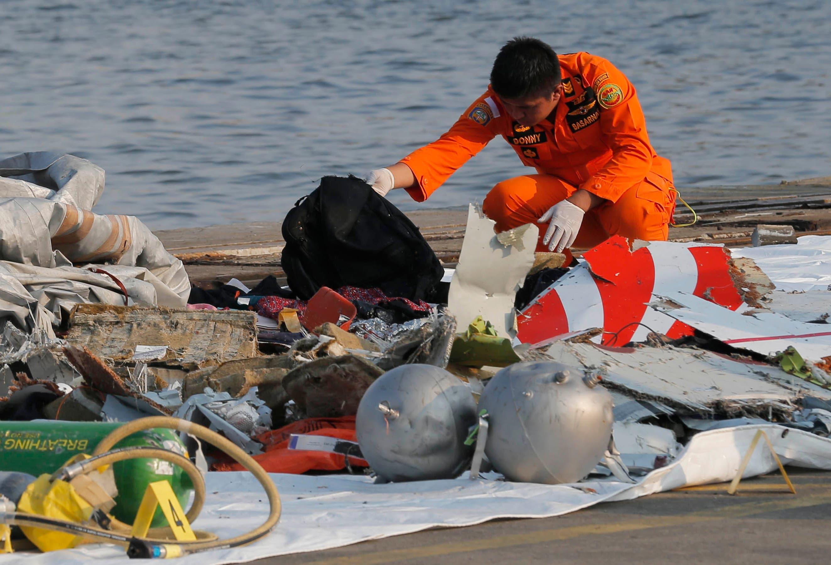 Ein Mitarbeiter der Rettungsdienste untersucht Trümmerteile. (Bild: AP Photo/Tatan Syuflana)