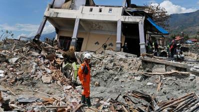 Ein Retter steht neben einem vom Erdbeben und dem anschliessenden Tsunami zerstörten Haus auf der indonesischen Insel Sulawesi. (Bild:Dita Alangkara/AP (Palu, 8. Oktober 2018))
