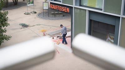 Ein Bauarbeiter kehrt vor der Wittenbacher Raiffeisenbank. Einen Tag nach dem Raubüberfall vom Montag hat der Alltag wieder Einzug gehalten. (Bild: Ralph Ribi)