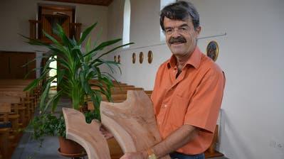 Peter Buchegger mit einer Skulptur aus Holz. (Bild: Monika Wick)