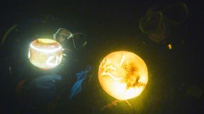 Zwei Taucher beleuchten mit ihren Lampen in dunkler Tiefe des Untersee ihre geschnitzten Rüben. (Bild: PD/Sandra Büchi)