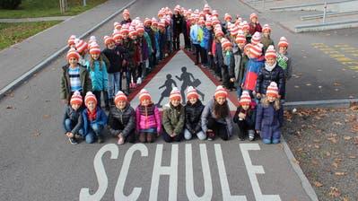 Mit den leuchtenden Pylonis-Mützen ausgerüstete Zuger Schüler. (Bild: Zuger Polizei)