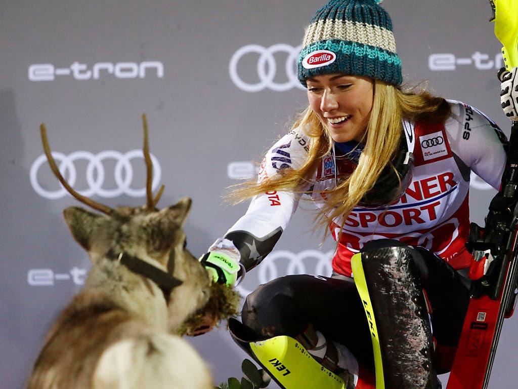 Mikaela Shiffrin füttert das Rentier, das sie dank ihrem Sieg in Levi gewonnen ha (Bild: KEYSTONE/AP/GABRIELE FACCIOTTI)