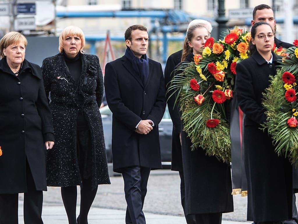 Macron (Mitte) auf dem Weg zur Neuen Wache, der zentralen Gedenkstätte in Deutschland für die Opfer von Krieg und Gewaltherrschaft. Dort legte er unter anderem mit Bundeskanzlerin Merkel (l.) und Bundestagsvizepräsidentin Roth (Grüne, 2. von links) Kränze nieder. (Bild: KEYSTONE/EPA/OMER MESSINGER)