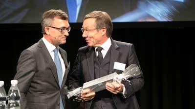 Nach zwölf Jahren ist Schluss: Kurt Weigelt nimmt von IHK-Präsident Roland Ledergerber das Abschiedsgeschenk entgegen. (Bild: Ralph Ribi)