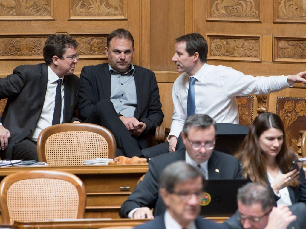 Diskussion in der SVP-Fraktion während der Budgetdebatte im Nationalrat: Parteipräsident Albert Rösti (BE), Marcel Dettling (SZ) und der Zuger Thomas Aeschi (von links) (Bild: KEYSTONE/PETER SCHNEIDER)