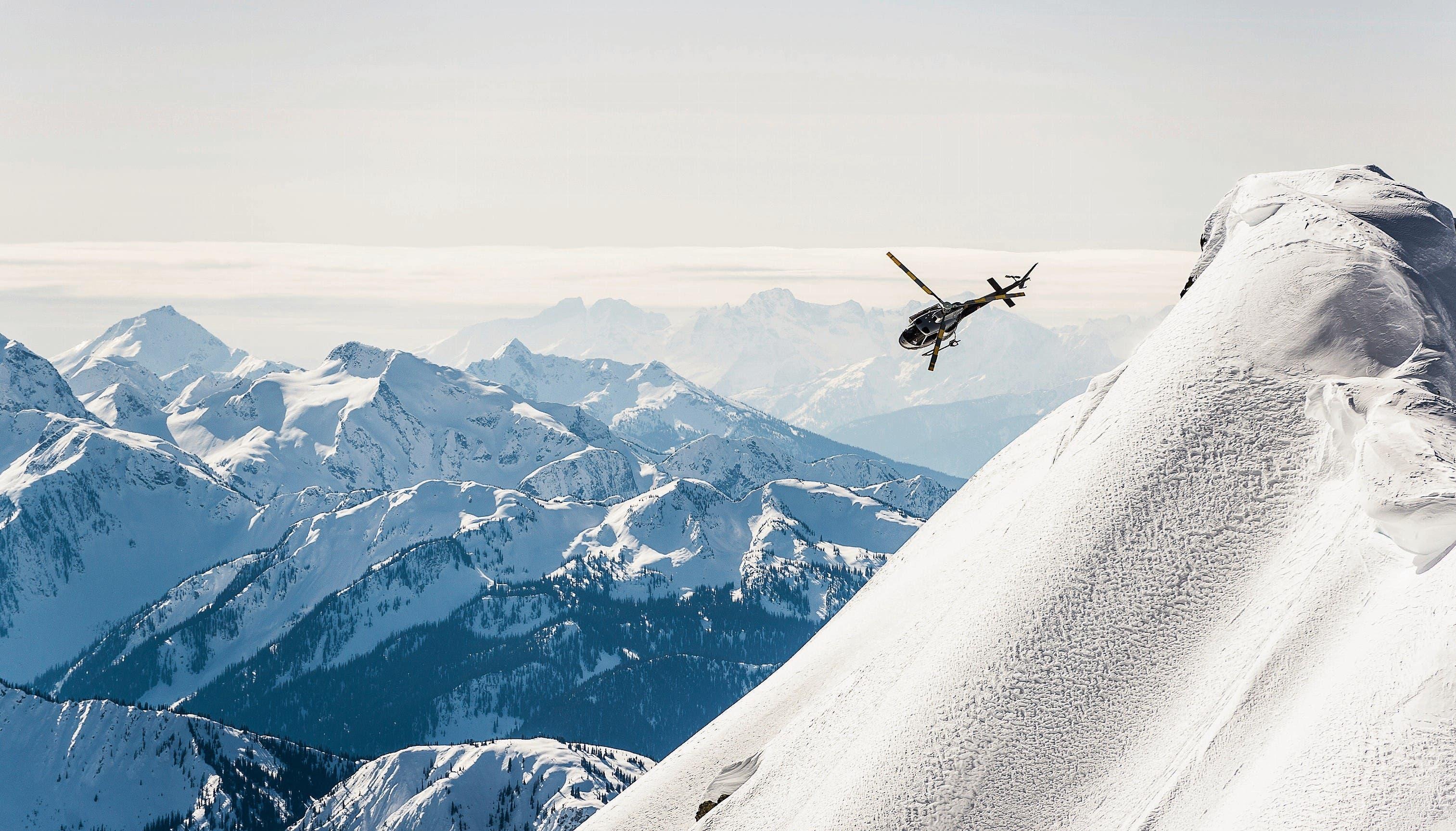 Mitten in den verschneiten Rocky Mountains: Helikopter beim Anflug auf eine Bergspitze im rund 2000 Quadratkilometer grossen Ski-Areal von Revelstoke. (Bild: Alain Sleigher/Selkirk Tangiers)