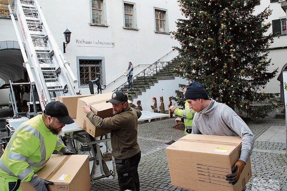 Die Mitarbeiter einer Zügelfirma laden Kartons auf Transportplattformen. Auch Mitarbeiter der Verwaltung tragen Kartons ins neue Domizil. (Bild: Martin Knoepfel)