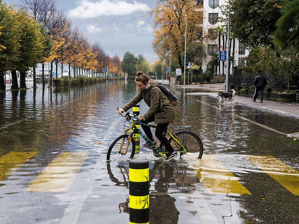 «Wasserrad Fahren» auf einer überschwemmten Strasse in Locarno. (Bild: KEYSTONE/TI-PRESS/ALESSANDRO CRINARI)