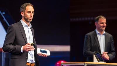 Adrian Bolliger (links), Chef Mobile Business Services bei Swisscom, präsentiert im KKL einen neuen Prototypen eines 5G-Handys. (Bild: Alexandra Wey/Keystone, 8. November 2018)