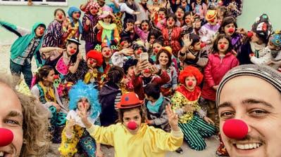 Spitalclown Kurt Bucher und Animator Gian Cadonau posieren mit syrischen Flüchtlingskindern. (Bild: ZVG)