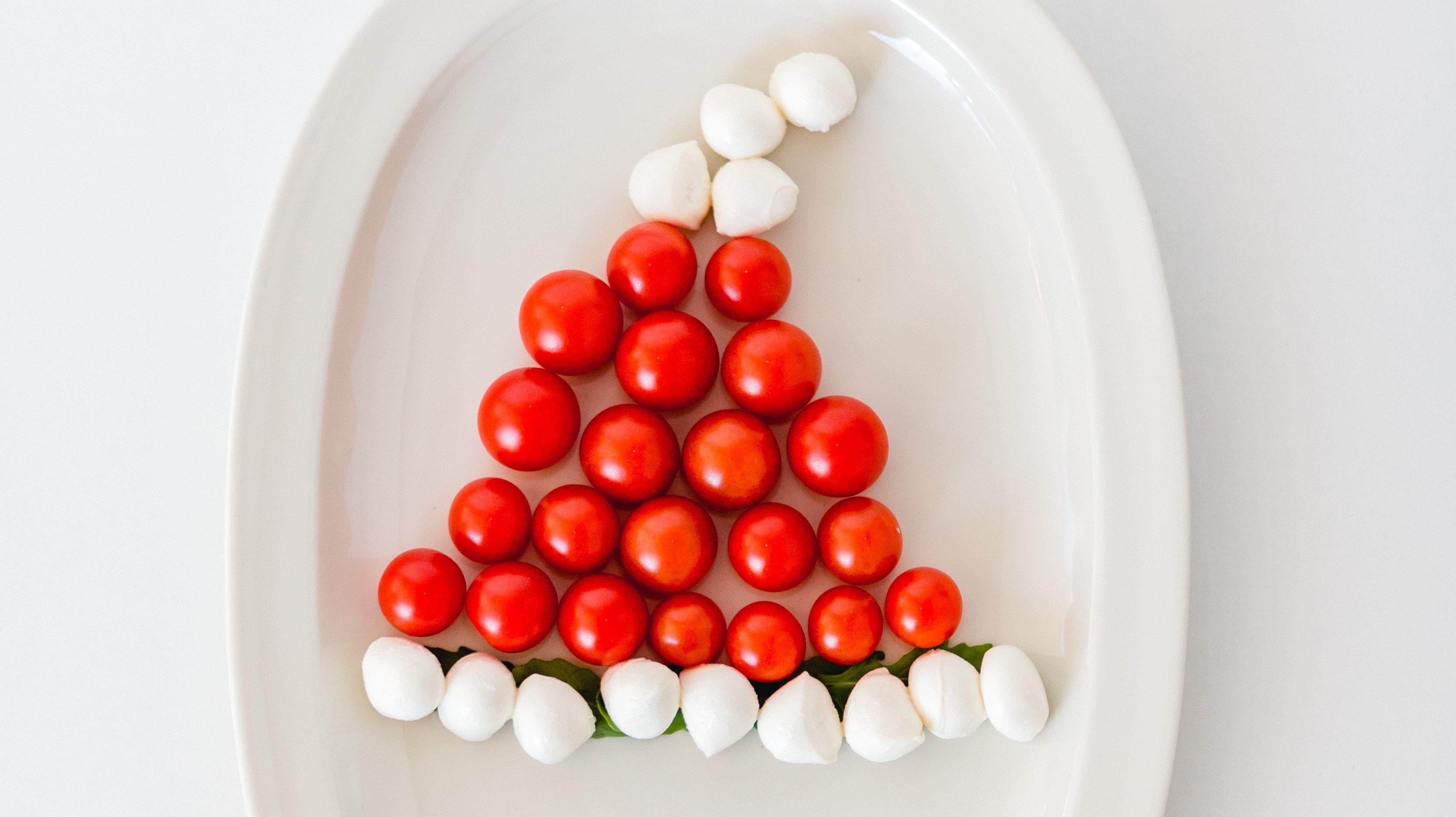 Zipfelmütze: Was der Weihnachtsmann auf dem Kopf trägt, lässt sich mit Cherrytomaten und Mozzarellakugeln darstellen.