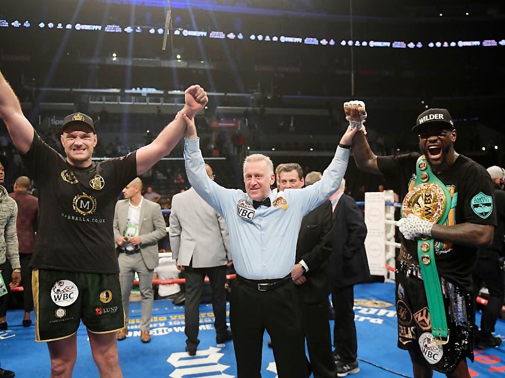 Der Ringrichter hebt für einmal die Hände von beiden Boxern nach dem Kampf: Tyson Fury (links) und WBC-Champion Deontay Wilder (rechts) fühlen sich gleichzeitig als Gewinner (Bild: KEYSTONE/AP/MARK J. TERRILL)