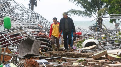 epa07246252 Indonesian men walk among debris after a tsunami hit the Sunda Strait in Pandeglang, Banten, Indonesia, 23 December 2018. According to the Indonesian National Board for Disaster Management (BNPB), at least 43 people dead and 584 others have been injured after a tsunami hit the coastal regions of the Sunda Strait.  EPA/ADI WEDA