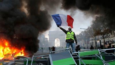 Ein Demonstrant schwenkt die französische Flagge auf der Champs-Elysees. (Bild: AP Photo/Michel Euler, File)