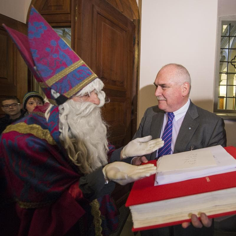 Der Luzerner Kantonsratspräsident Urs Dickerhof erhält vom Samichlaus ein grosses Buch mit dem Titel «AUS BILD UNG» (Bild: Keystone)