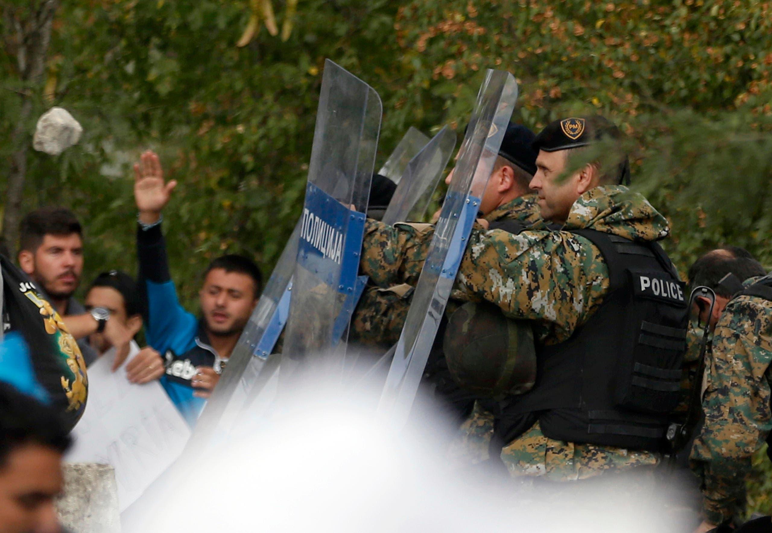 Ein Stein fliegt auf die Polizisten zu. (Bild: Keystone/AP Photo/Darko Vojinovic)