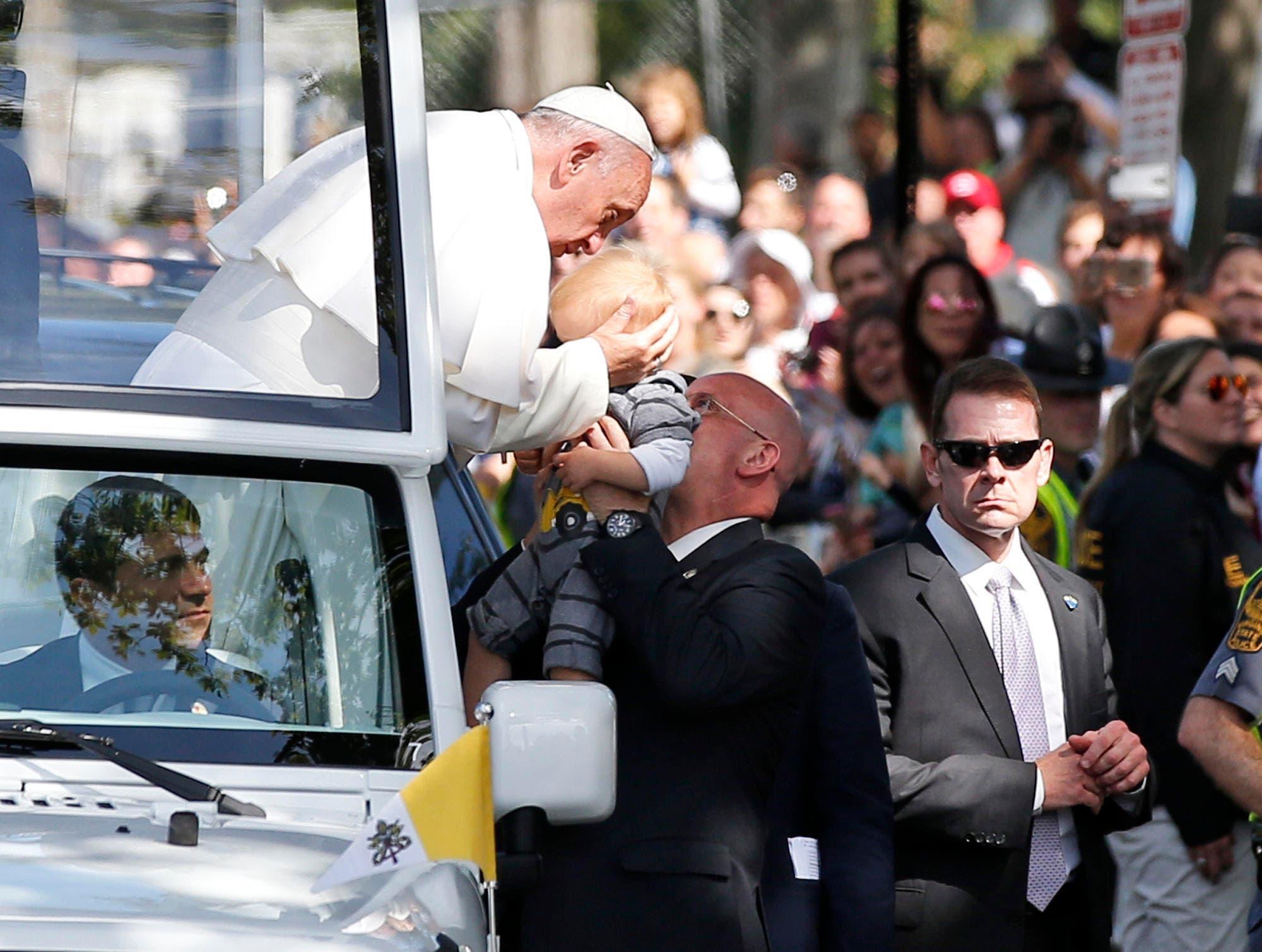 Der Chef der Gendarmerie bringt ein Kind aus der Menge zum Papst. (Bild: AP Photo / Alex Brandon / Pool)