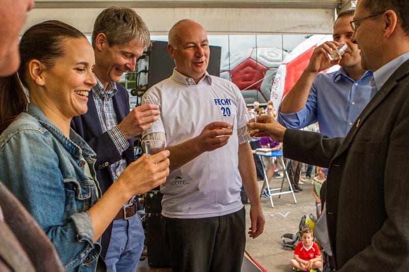 Anstossen mit Gemeindepräsident Kaspar Widmer (mit Fechy-Teamtrikot), Tourismusdirektor Marcel Perren (2.v.l.) und Sängerin Caroline Chevin (1.v.l.). (Bild: Stefan Krapf, Synor Media)