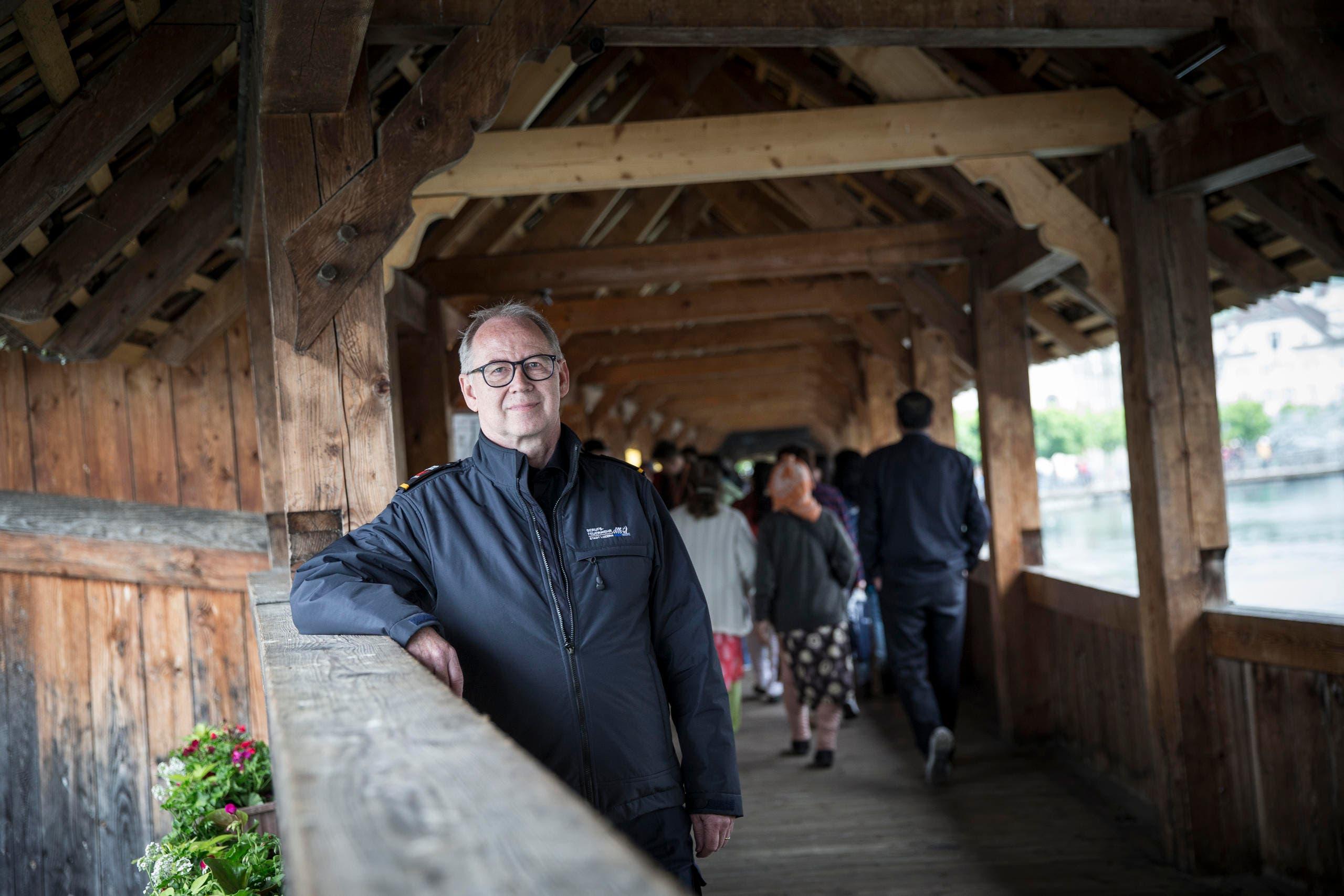 Feuerwehrkommandant Theo Honermann zeigt Brandschutzmassnahmen auf der Kapellbrücke. Im Hintergrund, kaum sichtbar, die Videokameras. (Bild: Manuela Jans-Koch (Luzern, 3. Mai 2018))