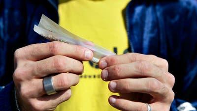 Ein Jugendlicher dreht sich einen Joint. Bild: Keystone