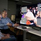 Martin Biallas (rechts) erklärt Testperson Beat Böschwie er mit seinen Hirnströmen einen TV steuern kann. (Bild: Corinne Glanzmann; Nottwil, 17. Mai 2018)
