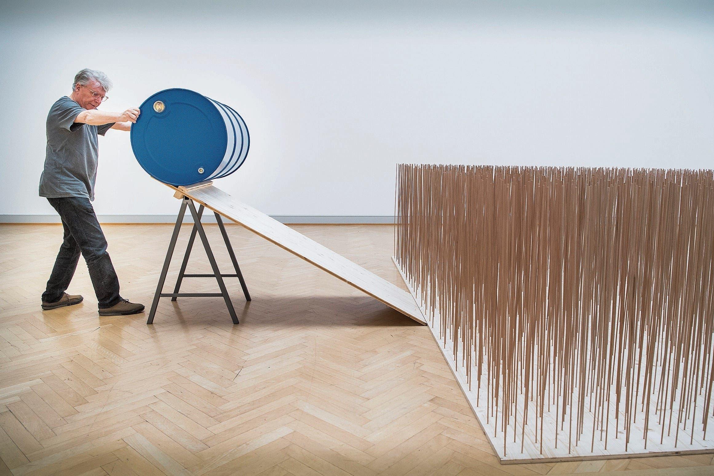 Roman Signer ist bereit, die Holzstäbe mit dem blauen Fass niederzumähen. (Bild: Ralph Ribi)