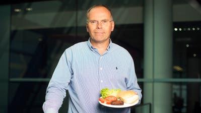 Der niederländische Physiologie-Professor Mark Post präsentiert seinen gezüchteten Rindfleischburger. (Bild:Simon Dawson/Bloomberg (London, 6. August 2013))