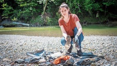 Annette Jenny zeigt zwei Schuhsohlen, die sie am Sitterufer eingesammelthat. (Bild: Urs Bucher)