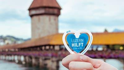 Eine Helferin verkauft am Luzerner Fest zwei BesuchernFestabzeichen. (Bild: PD)