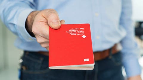 Ein Mann zeigteinen biometrischen Schweizer Pass. Bild: Christian Beutler/Keystone