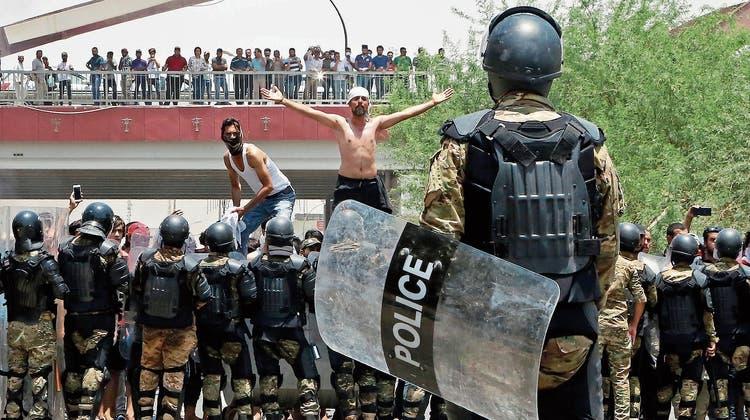Polizisten halten in Basra Demonstranten von zentralen Regierungsgebäuden fern. (Bild: AP; 15. Juli 2018)