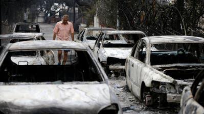 Ein Mann läuft in Mati, östlich von Athen, an ausgebrannten Autos vorbei.(Bild: AP Photo/Thanassis Stavrakis, 24. Juli 2018)