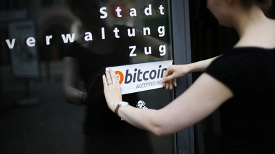 Eine Mitarbeiterin der Zuger Stadtverwaltung bringt einen Bitcoin-Kleber an. Die Stadt äussert sich nun zu einem potenziellen Reputationsrisiko. (Bild: Stefan Kaiser (Zug, 1. Juli 2016))