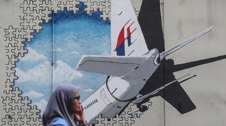 Eine Frau läuft am Wandbild zur Erinnerung an den Absturz des MH370-Fluges vorbei. (Bild: EPA/ FazryIsmail, Kuala Lumpur, 29. Juli 2018)
