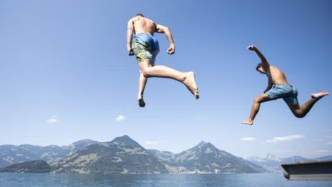 Junge Männer springen bei Beckenried im Kanton Nidwalden in den Vierwaldstättersee. Die Wettervorhersage verspricht heisses Sommerwetter während den nächsten Tagen.(Bild: Urs Flüeler/Keystone (Beckenried, 30. Juli 2018))
