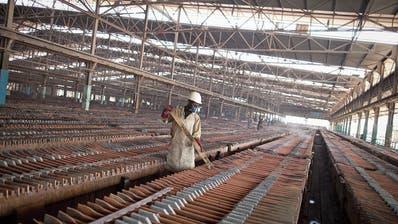 Ein Arbeiter in der kongolesischen Provinz Katanga kontrolliert Kupferplatten. (Bild: Simon Dawson/Bloomberg; Kolwezi, 1. August 2012)