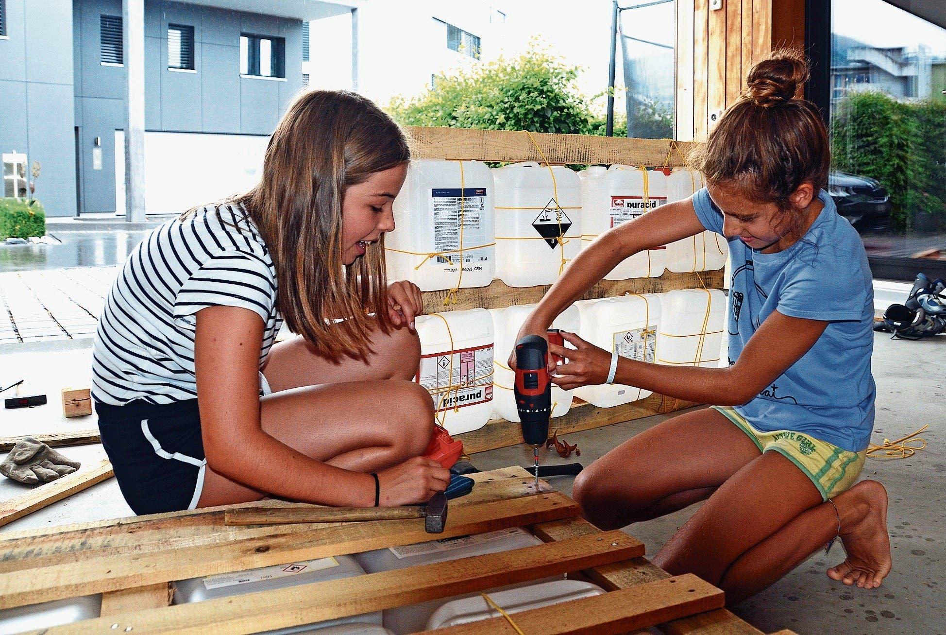 Aus Paletten und Kanistern bauen sich zwei Teilnehmerinnen der Chübelregatta einen schwimmenden Untersatz. (Bild: Bilder: Corinne Hanselmann)
