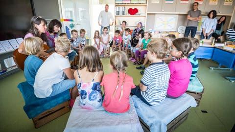 Die 1.- und 2.-Klässler singen mit ihren Lehrerinnen Ursula Bollack und Mirjam Walter zum Schulanfang. Die Eltern hören zu. (Bild: Andrea Stalder)