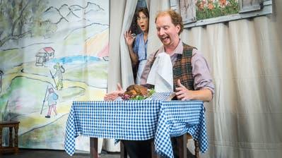 Doris Haudenschild führt als hinterlistige Wirtin Böses im Schild, während Jan Opderbeck als Schneidersohn nichts ahnend sich von seinem Tischlein ein gebratenes Poulet aufdecken lässt. (Bild: Andrea Stalder)