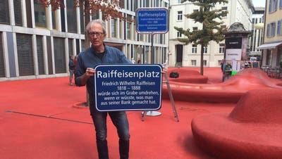 Der St.Galler Historiker überklebte am Montag die Namenstafel des Raiffeisenplatzes mit seiner eigenen Version. (Bild: Christoph Renn)