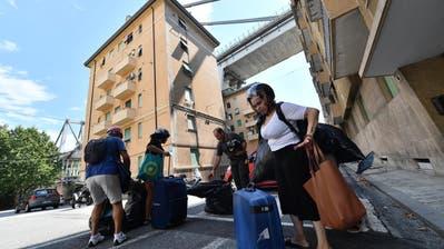 Feuerwehrleute evakuieren Bewohner am 16. August aus den Häusern unter der Morandi-Brücke. Die italienischen Behörden befürchten, dass weitere Teile derBrücke einstürzen könnten. (Bild: EPA / LUCA ZENNARO)