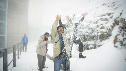 Schwägalp im Sommer vor zwei Jahren: Touristen aus Bangladeschfreuen sich über den Schneeauf dem Säntis.(Bild: Ralph Ribi/14. Juli 2016)