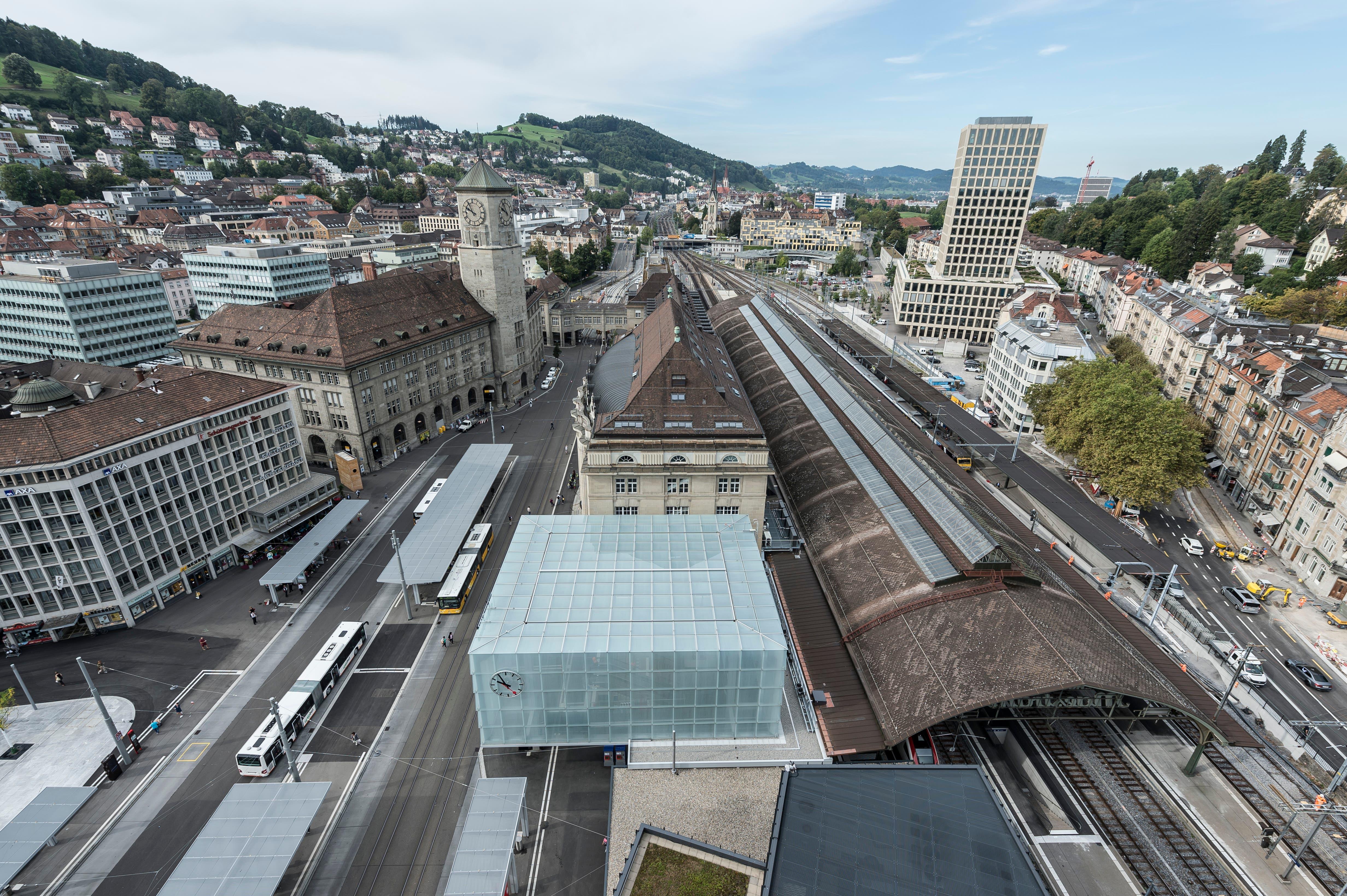 Blick Richtung Westen über die neue Ankunftshalle und das Bahnhofsgebäude. Rechts hinter dem Bahnhof das Hochhaus der Fachschule St.Gallen (FHS). (Bild: Hanspeter Schiess - 29. August 2018)