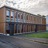 Grosse Fenster und die Holzfassade dominieren beim Betrachten des neuen Schulhauses. (Bilder: Reto Martin)