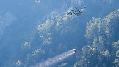 Ein Helikopter transportiert Löschwasser, um den Brandherd nach einem Kleinflugzeugabsturz am Lopper in Hergiswil im Kanton Nidwalden zu löschen.(Bild: Keystone/Urs Flüeler)