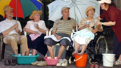 Senioren kühlen ihre Beine im Hitzesommer 2003: Nach jener Hitzewelle führten die Westschweizer Kantone Hitzepläne ein. Jetzt ziehen die Deutschschweizer langsam nach.(Bild: Keystone/DPA/Waltraud Grubitzsch; Leipzig, 7. August 2003)