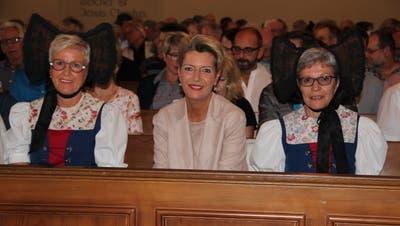 Karin Keller-Sutter, flankiert von zwei Ehrendamen in Tracht, in den Bänken der evangelischen Kirche Arbon. (Bild: Hedy Züger)